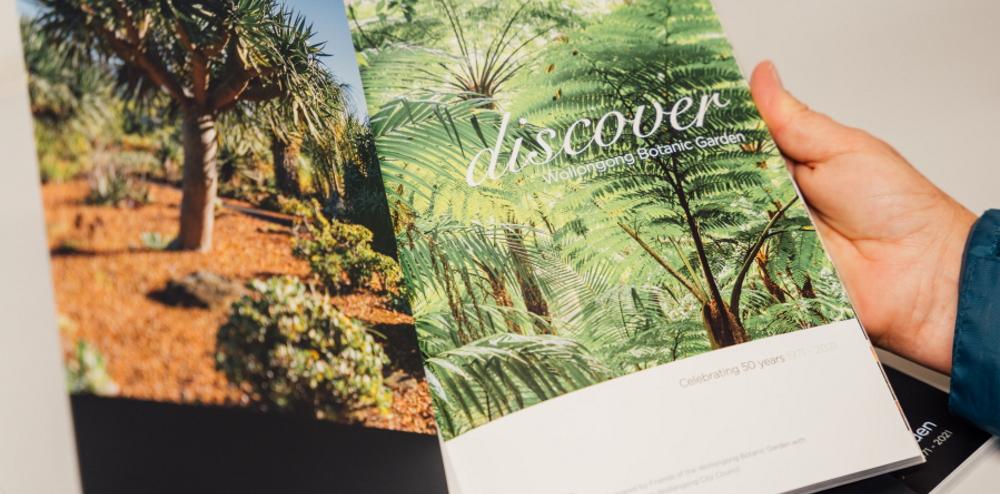 Person holding the Discover Wollongong Botanic Garden Book