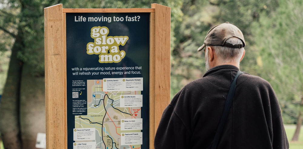 Man looking at sign for Go Slow for a 'Mo Nature Wellness Trail